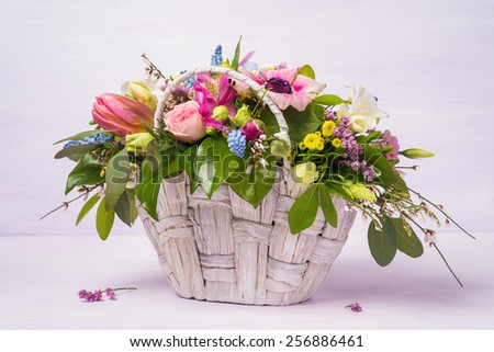 Beautiful bouquet of spring flowers in a wicker basket (Anemone, muscari, freesia, tanacetum, genesta, limonium, vaksflauer, tulips) - stock photo