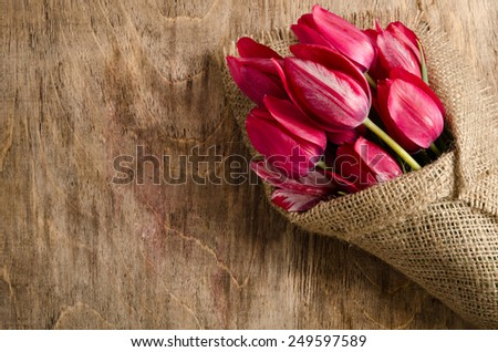 Beautiful bouquet of tulips wrapped in burlap on the wooden table - stock photo