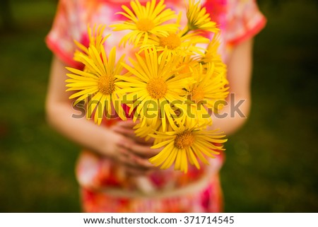 Beautiful bouquet of yellow flowers in hands of the girl - stock photo