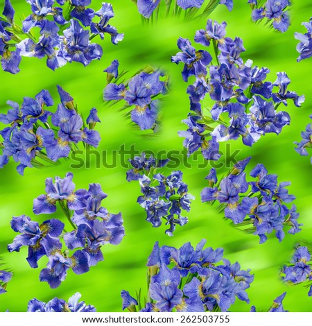 Beautiful bouquets of blue irises on green blurred background. Seamless pattern