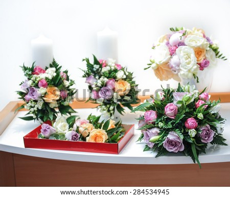 Beautiful bouquets of rose flowers, on table. Wedding bouquets of different colors roses. Elegant wedding bouquets on table at restaurant - stock photo