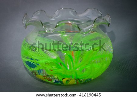 Beautiful bowl with colored stones and a plant for fish. This fish tank is also useful in air conditioner rooms.  - stock photo