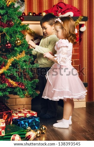 beautiful boy and girl decorate christmas tree - stock photo
