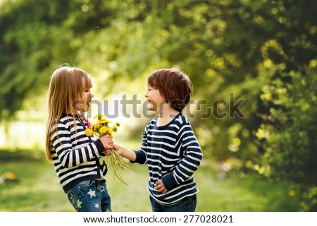 Beautiful boy and girl in a park, boy giving flowers to the girl. Friendship concept - stock photo