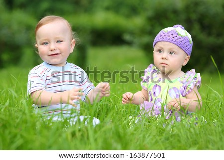 Beautiful boy and girl sitting on fresh green grass in the meadow