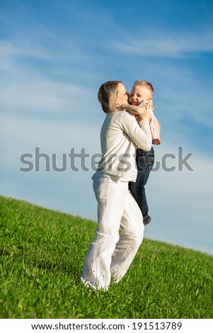 Beautiful boy and mom playing in spring park. Happy family concept.
