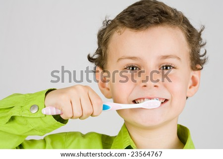 Beautiful boy brushing teeth, isolated on white