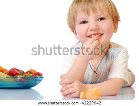beautiful boy eating mandarin with plate with fruits on the background isolated on white.