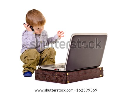 Beautiful boy gesticulating hands speaks on the phone looking at laptop - stock photo