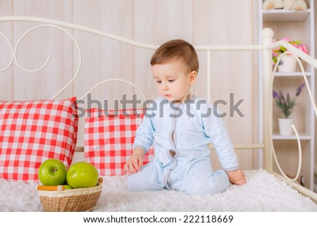 beautiful boy in pajamas on the bed in the nursery