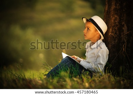 beautiful boy in the white hat reading a book under a tree and thinking, relaxed looking up and holding a book - stock photo