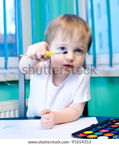 Beautiful boy painting with watercolors - stock photo