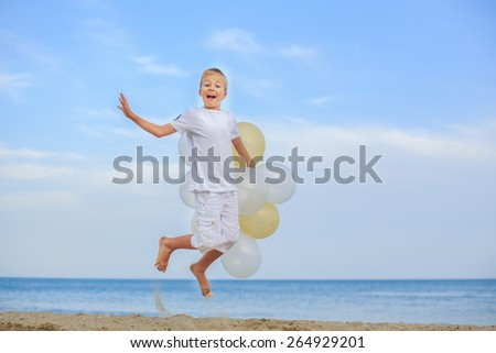 Beautiful boy play with a beach balloons outdoors  - stock photo