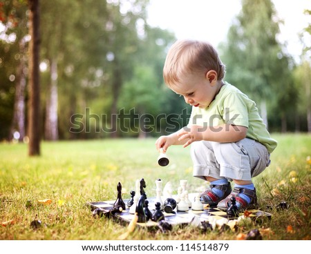 beautiful boy playing chess in summer park - stock photo