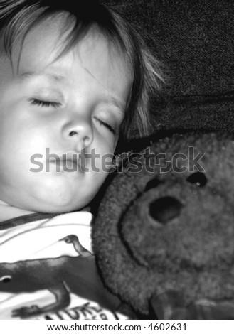 Beautiful Boy sleeping with his stuffed bear, black and white photo - stock photo