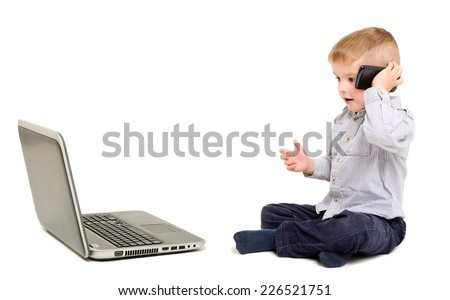 Beautiful boy talking on the phone sitting next to a laptop - stock photo