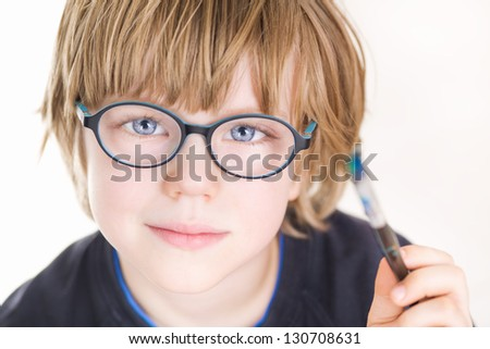 Beautiful boy with glasses and painting brush in hand - stock photo