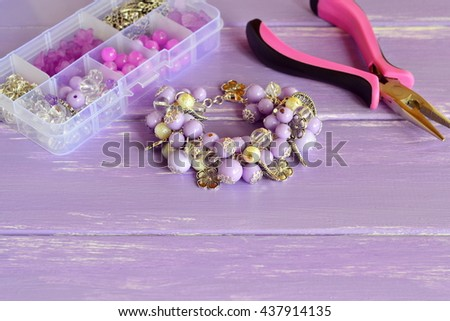 Beautiful bracelet with lilac and white plastic beads, metal flowers and leaves. Organizer with different beads, steel decorative pendants and rings. Pliers. Homemade jewelry concept  - stock photo