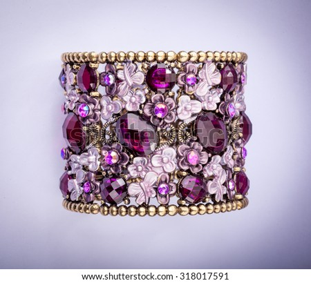 Beautiful bracelet with precious stones on color background. - stock photo