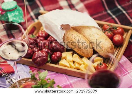 Beautiful bread with different food lies in the basket on the plaid