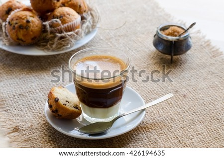 Beautiful  breakfast. Glass cup of coffee with condensed milk served with little chocolate muffin and brown sugar  on sacking background.  - stock photo