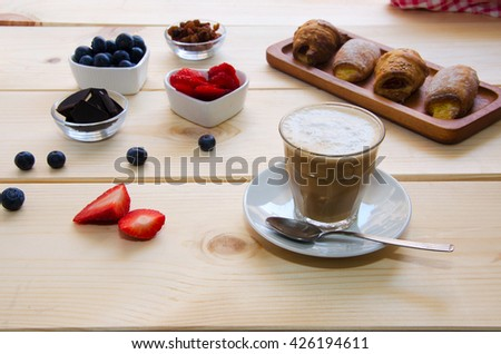 Beautiful  breakfast. Glass cup of coffee with milk served with crushed chocolate, different pastries, berries and raisins on the wooden background.  - stock photo
