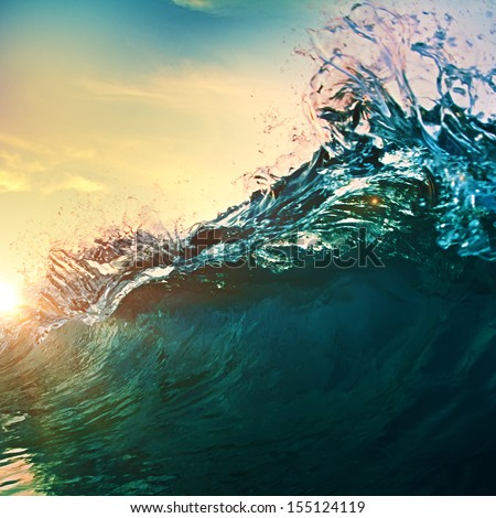 beautiful breaking surfing ocean wave closing at sunset time near tropical shore - stock photo