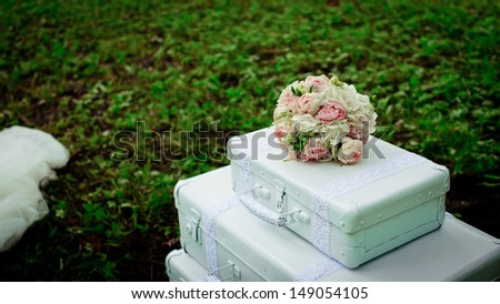 Beautiful bridal bouquet is lying on the vintage shabby suitcase at ferrous stand in the park - stock photo