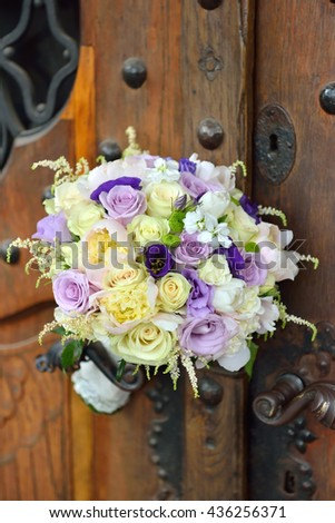 Beautiful bridal bouquet of colored roses lies on the wood door handle. Symbol of purity - stock photo