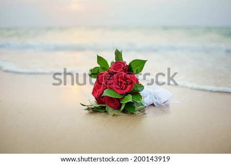 Beautiful bridal bouquet of red roses and on a tropical beach. - stock photo