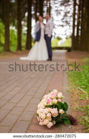 beautiful bridal bouquet of roses at a wedding party with rings - stock photo