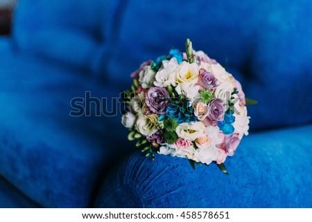 Beautiful bridal bouquet on deep blue sofa. Wedding concept - stock photo