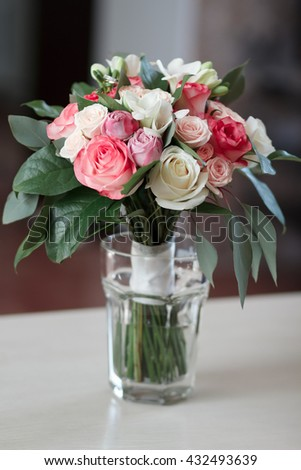 beautiful bridal bouquet standing in a glass on a wooden table, wedding bouquet of roses, freesias and carnations - stock photo