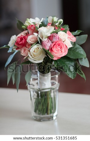 beautiful bridal bouquet standing in a glass on a wooden table, wedding bouquet of roses, freesias and carnations