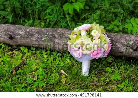 Beautiful bridal bouquet standing on the grass - stock photo
