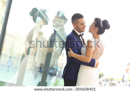 Beautiful bridal couple embracing in city