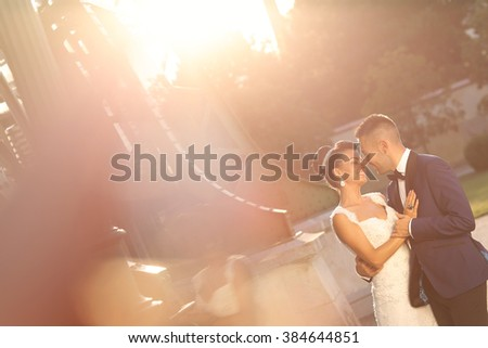 Beautiful bridal couple embracing in city - stock photo
