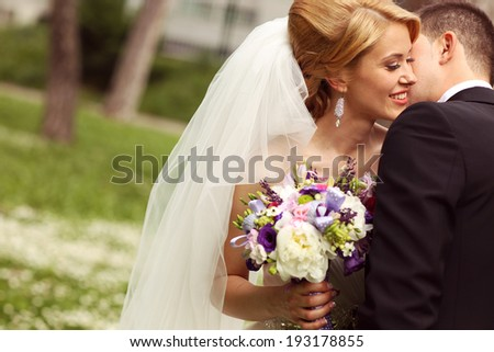 Beautiful bridal couple having fun in the park on their wedding day