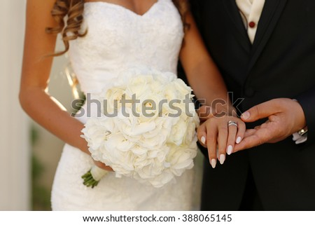 Beautiful bridal couple holding hands on wedding day
