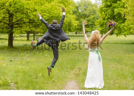 beautiful bride and groom after wedding on a green meadow - stock photo