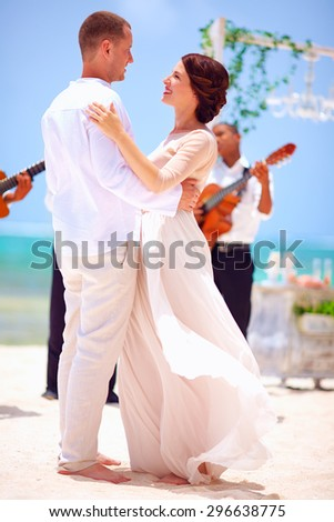 beautiful bride and groom dancing on tropical beach, caribbean wedding - stock photo
