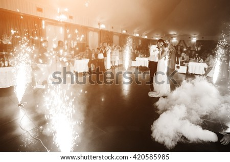beautiful bride and groom dancing the first dance between fireworks - stock photo