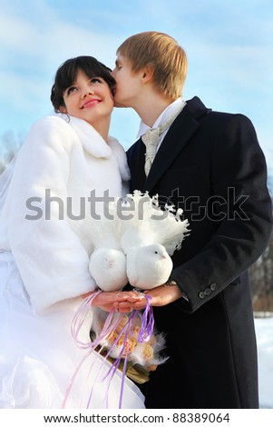 beautiful bride and groom hold pair of white doves at winter outdoors; man kisses woman - stock photo