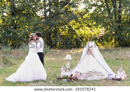 Beautiful bride and groom hugging on their wedding day, photo session in the nature