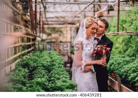 Beautiful bride and groom kissing and huging in the greenhouse - stock photo