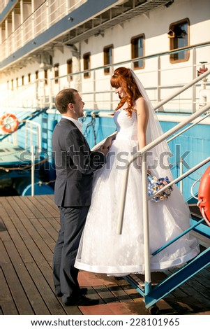 Beautiful bride and groom looking at each other on deck of cruise ship - stock photo