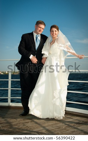 Beautiful bride and groom on the deck near river - stock photo