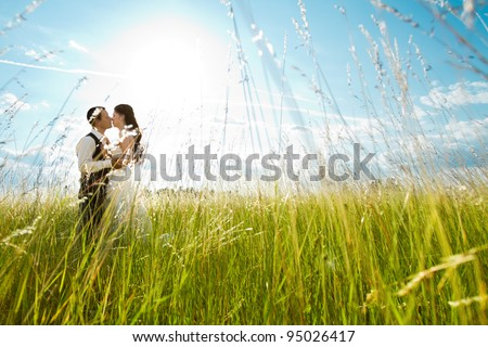 Beautiful bride and groom standing in grass and kissing. Wedding couple fashion shoot - stock photo