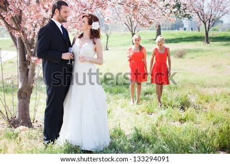Beautiful Bride and Groom under a cherry tree with champagne - stock photo