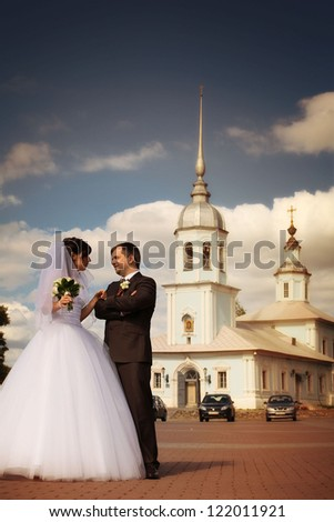 Beautiful bride and groom walk around the city - stock photo